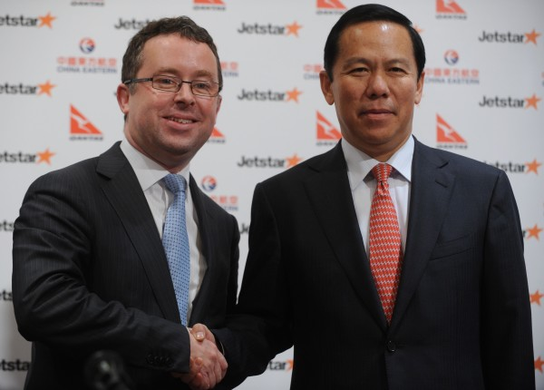 Qantas CEO Alan Joyce (L) and China Eastern Airlines Ltd chairman Liu Shaoyong shake hands at a press conference in Hong Kong 26/03/2012. Both companies will launch a new Hong Kong based budget airline in 2013 aimed at cashing in on China's booming aviation market.